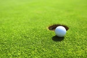 Golf ball on edge of hole